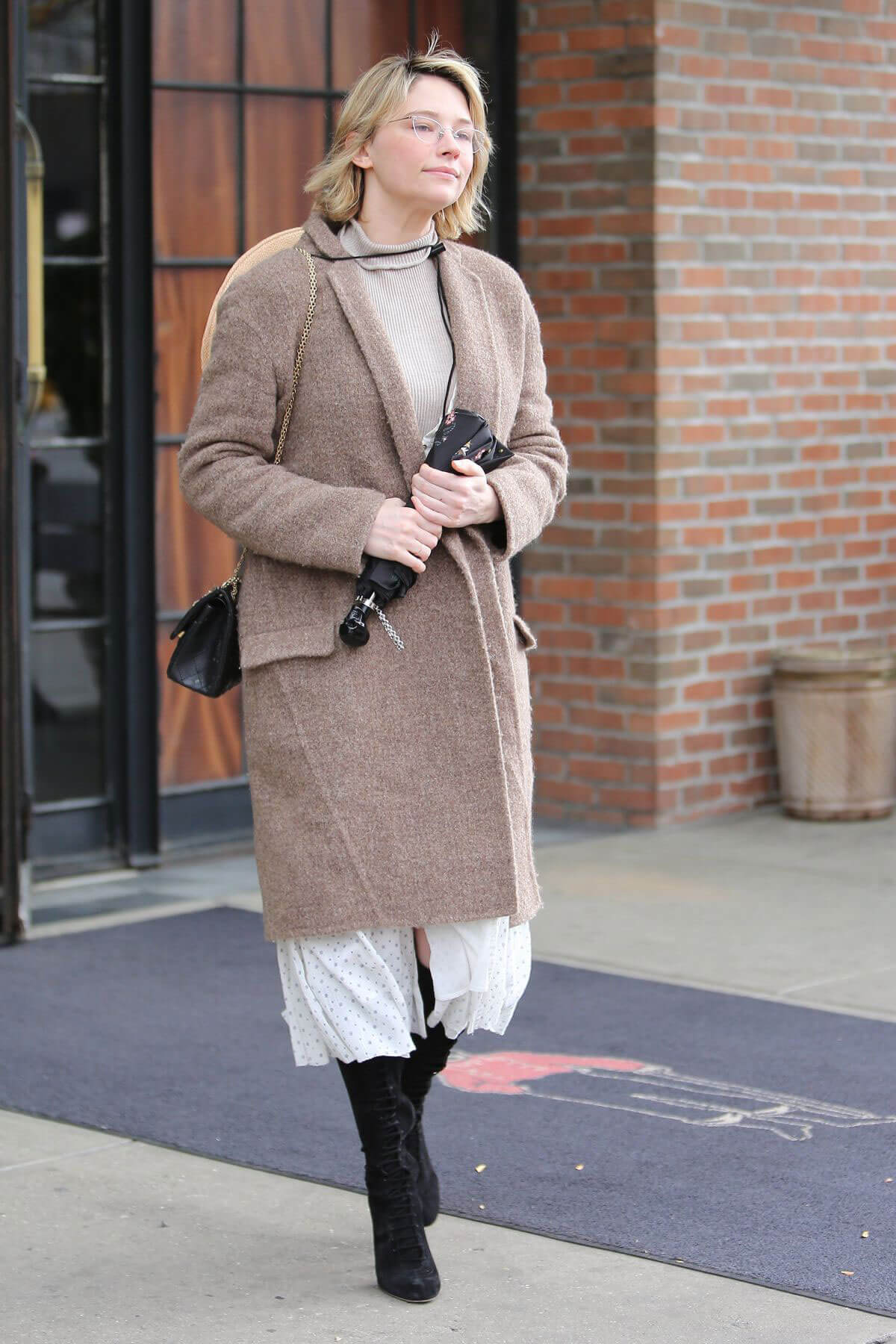 Haley Bennett wears Winter Coat & Long Boots Leaves Her Hotel in New York