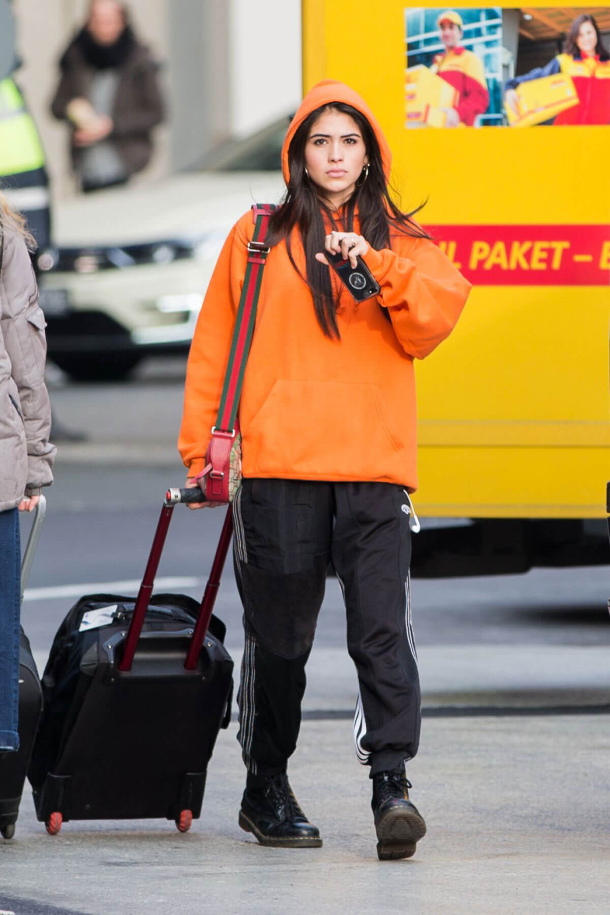 Kim Turnbull wears Orange Color Hoodie and Black Lower at Tegel Airport in Berlin