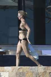 Charlize Theron Stills in Black Bikini on the Beach in Los Cabos