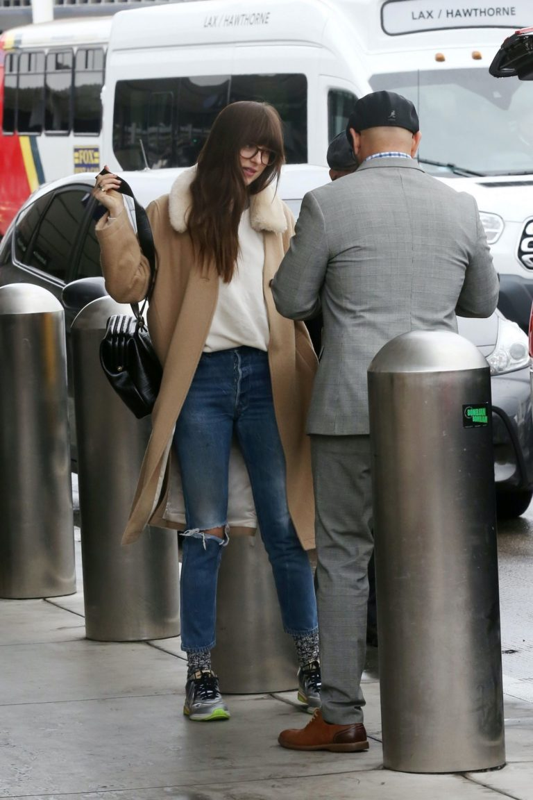 Dakota Johnson in white top and ripped jeans with long coat out in Los Angeles 2019/11/27 2