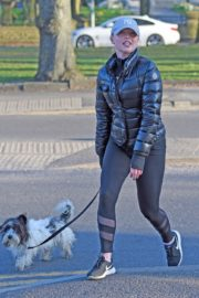Jorgie Porter in puffer jacket and tights during jogging with her dog in Manchester 2020/03/29 13