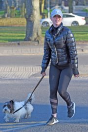 Jorgie Porter in puffer jacket and tights during jogging with her dog in Manchester 2020/03/29 16
