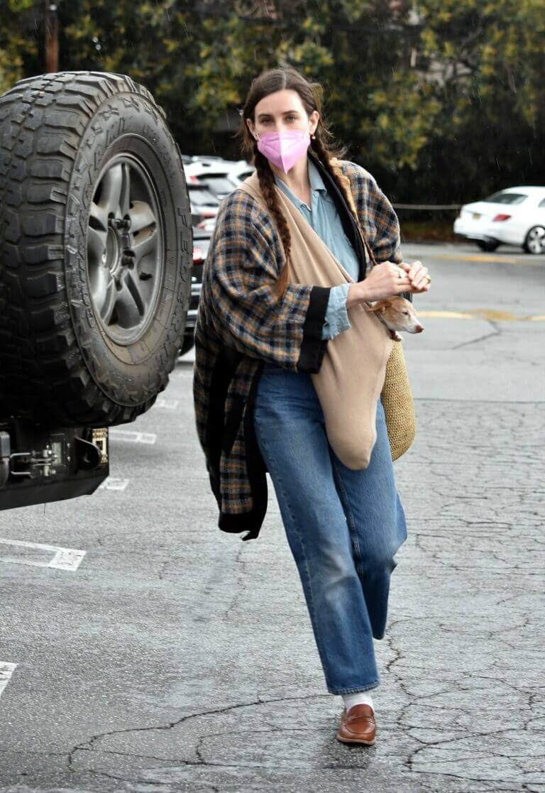 Scout Willis sweetly covers her pet from the rain at Brentwood Country Mart 03/10/2021 2